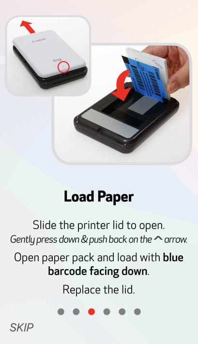 Load Paper: Slide the printer lid to open. Gently press down and push back on the (up) arrow. Open paper back and load with the blue barcode facing down. Replace the lid.